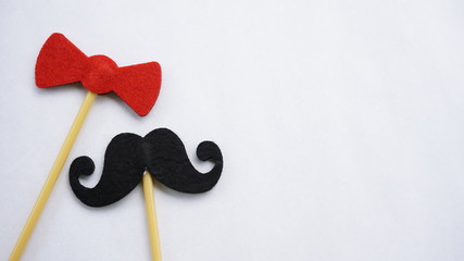 Top or flat lay view of Photo booth props red bow tie and a black mustache on a white background flat lay. Birthday parties and weddings.