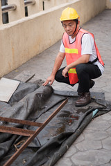 construction worker inspecting pile of raw material