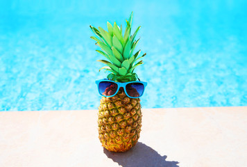 Fashion pineapple with sunglasses on a blue water pool background, summer holidays, vacation and food concept