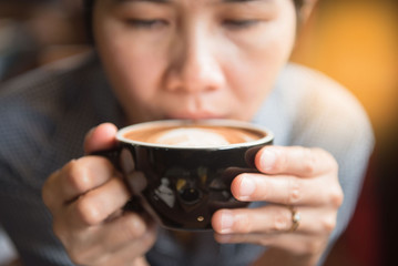 Women holding a hot cup of coffee in hands in coffee shop at morning  .