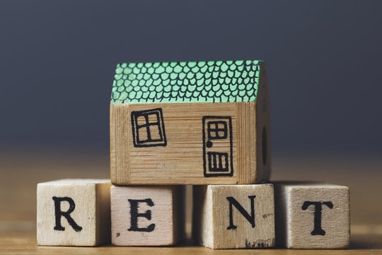 Home rent concept. House model with rent word made from wooden blocks.
