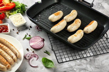 Composition with delicious fried sausages on grill pan