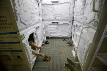An IT employee takes off shoes as he prepares to sleep in a capsule bed unit at Xiangshui Space in Beijing
