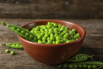 Bowl with fresh green peas on wooden background
