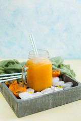 Apricot juice with ice in a jar on blue background