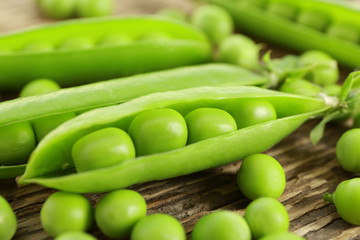 Fresh green peas on wooden background, closeup