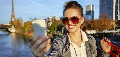 trendy woman with shopping bag taking selfie with phone in Paris