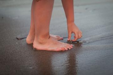 Children legs on a beach