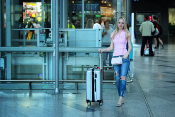 Young beautiful blonde girl standing close up with her silver suitcase in the airport