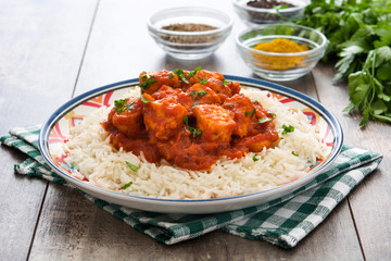 Chicken tikka masala with basmati rice on wooden table