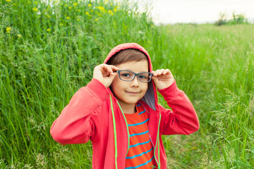 Child with glasses explores the forest and grass. A little boy goes camping. Nature with kids.