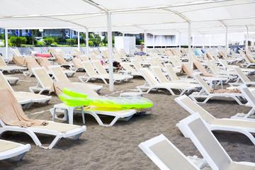 White plastic sunbeds in sandy beach under big parasol