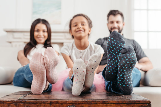 happy multicultural family in colorful socks sitting on sofa together