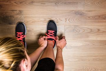 Junge Frau Bindet sich die Schuhe und ist Ehrgeizig für neue Ziele