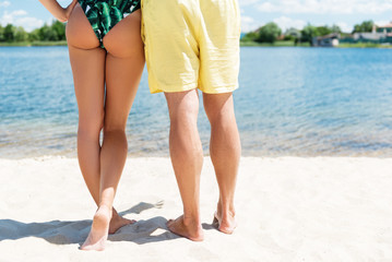 Youthful girl and guy resting on coastline outdoor