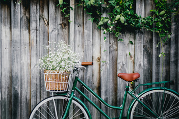 Bicycle against wooden fence with flowers in basket