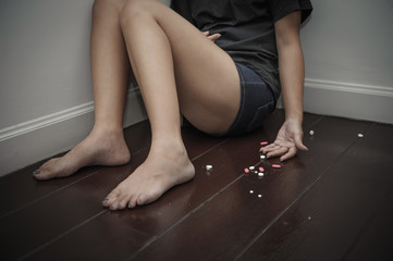 young woman lose consciousness with a lot of pills spilled on the floor, Suicide concept