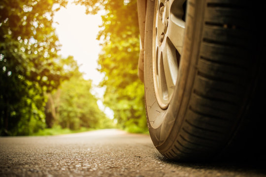 Wheel of cars on asphalt road on summer day in countryside green forest, nature street