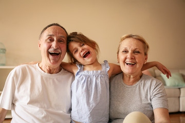 Playful grandparents with their granddaughter.