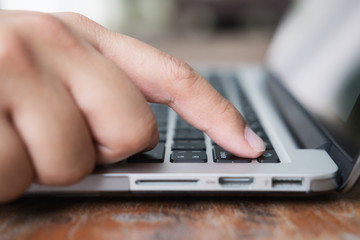 Selective focus on asian man's hand pressing laptop keyboard on power button. Online shopping