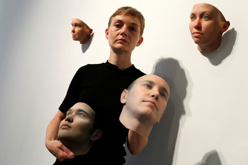 Artist Heather Dewey-Hagborg poses with various 3-D printed masks at the Fridman gallery in New York City