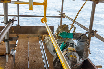 Painted, corroded, anti-corrosion, with spray guns on the production platform to extend the life of materials, Energy and petroleum industry sea offshore