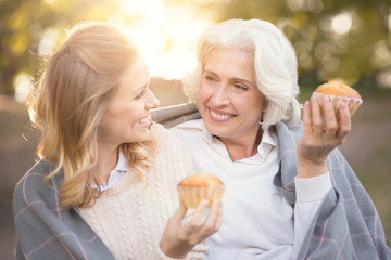 Smiling woman spending picnic with old mother outdoors