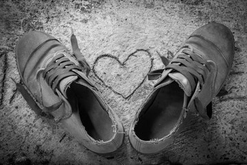 Old shoes with heart shape on cement floor , black and white vintage style