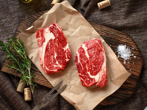 Raw fresh Chuck roll steak with herbs and salt on a cutting Board