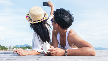 Young couple of lover laying down on the wooden floor near the beach taking themselves a photo