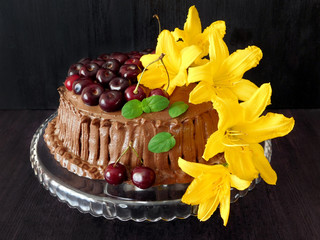 Chocolate cake decorated with cherries and flowers for a birthday party on a dark background