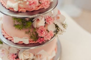 Beautiful white and colored wedding cake. A bride and a groom is cutting their wedding cake