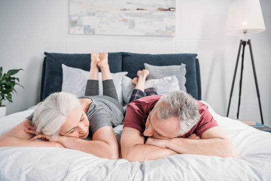 senior wife and husband sleeping in bed together at home