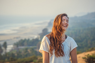 Girl laughs against the sea and the hills in Goa