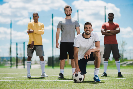 multiethnic soccer team standing on soccer pitch after game