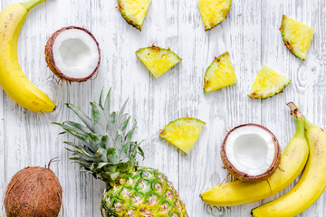 Concept of summer tropical fruits. Pineapple, banana, cocount on wooden background top view copyspace