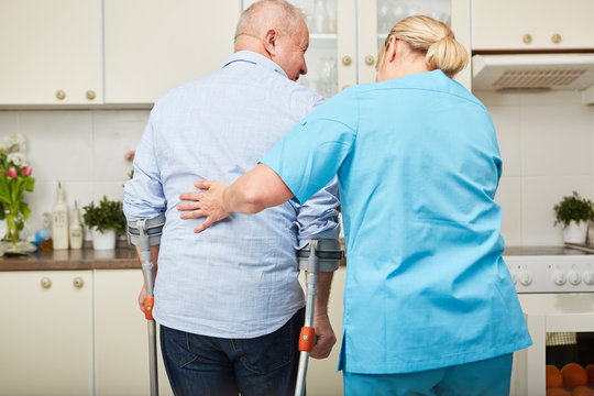 Physiotherapeutin hilft krankem Senior