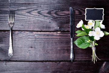 Iron fork and knife with a bouquet of jasmine