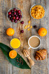 Light summer breakfast. Muesli, oranges, cherry, croissant and coffee on wooden table background top view