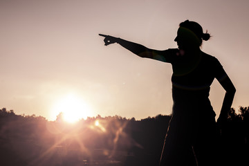 Woman silhouette enjoying the sunset light outdoor. Embracing nature. Victorious in sports competition. Visual effects