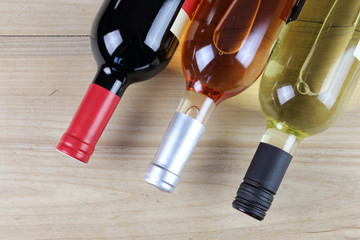 three wine bottles: red wine, white wine, and rose wine