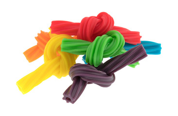 A group of colorful spiral licorice sticks tied in knots isolated on a white background.