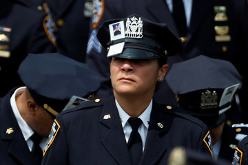 Officers wear images of slain New York City Police Department (NYPD) officer Miosotis Familia on their caps as they emerge from her funeral service at the World Changers Church in the Bronx borough of New York City