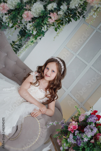 59da6bd573680 Beautiful little girl with curls and white Quinceanera dresses with a train  on the couch with flowers