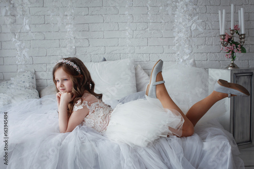 cf436df5c0879 Beautiful little girl with curls and white Quinceanera dresses with a train  on a white bed swinging his legs
