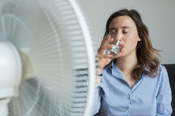Young woman refreshing in front of cooling fan