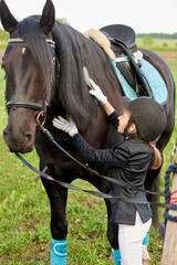 Pretty little girl jockey attend and brushing her horse