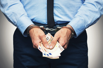 corruption and bribery concept - arrested official with money in hands