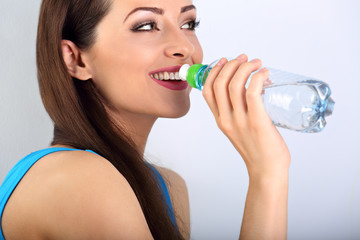 Beautiful happy toothy smiling makeup woman drinking water from the bottle. Healthy face skin. Closeup portrait.