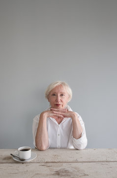 Portrait of senior woman sitting against gray wall